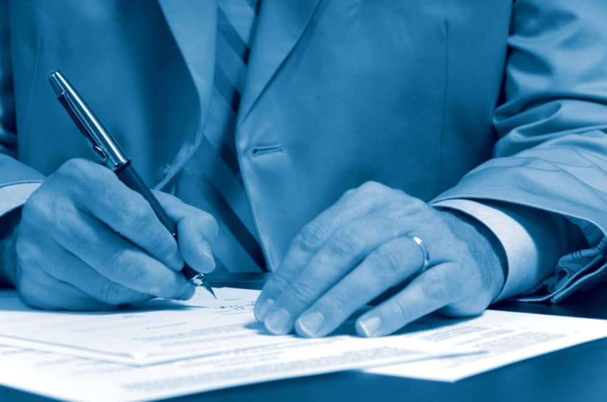 Business man in suit signing a contract or document